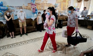 A nurse carries a newborn to meet its parents as foreign couples wait to collect their babies at Hotel Venice, owned by BioTexCom clinic in Kiev