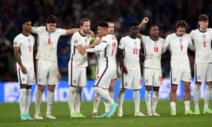 Jadon Sancho of England is consoled by is teammates after failing to score during the penalty shoot out.