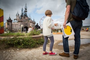 Visitors approach the fairytale castle at Dismaland.