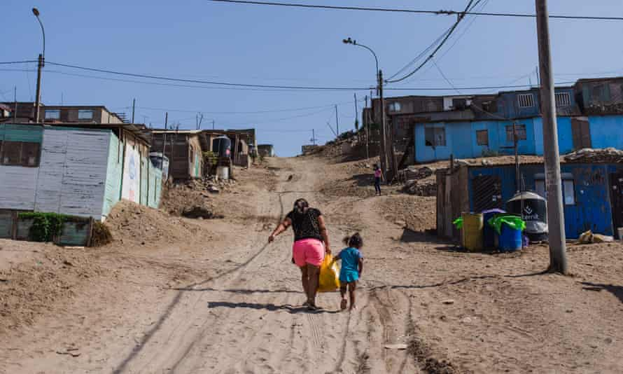 A woman and a small child walk up a dusty road carrying a heavy bag in a shantytown on the northern edge of Lima that is home to Nilda López.