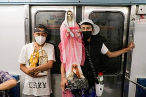 Mexico City, Mexico. Two young men carry a figure of Santa Muerte inside a metro carriage
