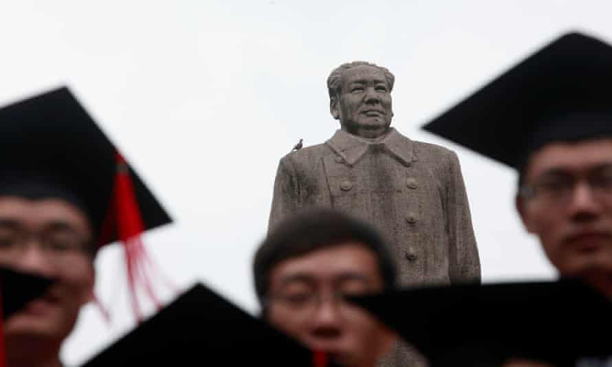 Graduates pose in front of a statue of the late Chinese leader Mao at Fudan University in Beijing.