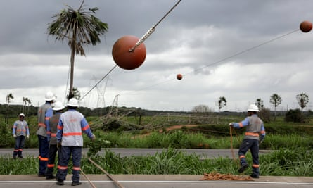 Technicians work on the site where a power transmission tower was damaged by a bomb in the outskirts of Fortaleza