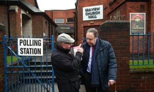 Nigel Dodds chats to local people outside Seaview church hall polling station in north Belfast.