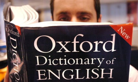 """A man reading a copy of the Oxford Dictionary of English. """"Post-truth"""" has been named as Oxford Dictionaries' word of the year after a spike in its use around the Brexit vote and Donald Trump's presidential bid. The phrase has long applied to climate denial as well."""