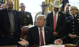 Trump vetoes Congress, surrounded by law enforcement officials.