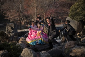 A bride and groom throw water as they pose for photos in a park