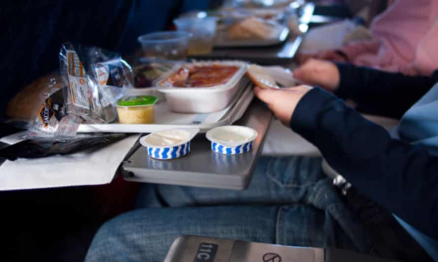 Passengers eating food on a plane.