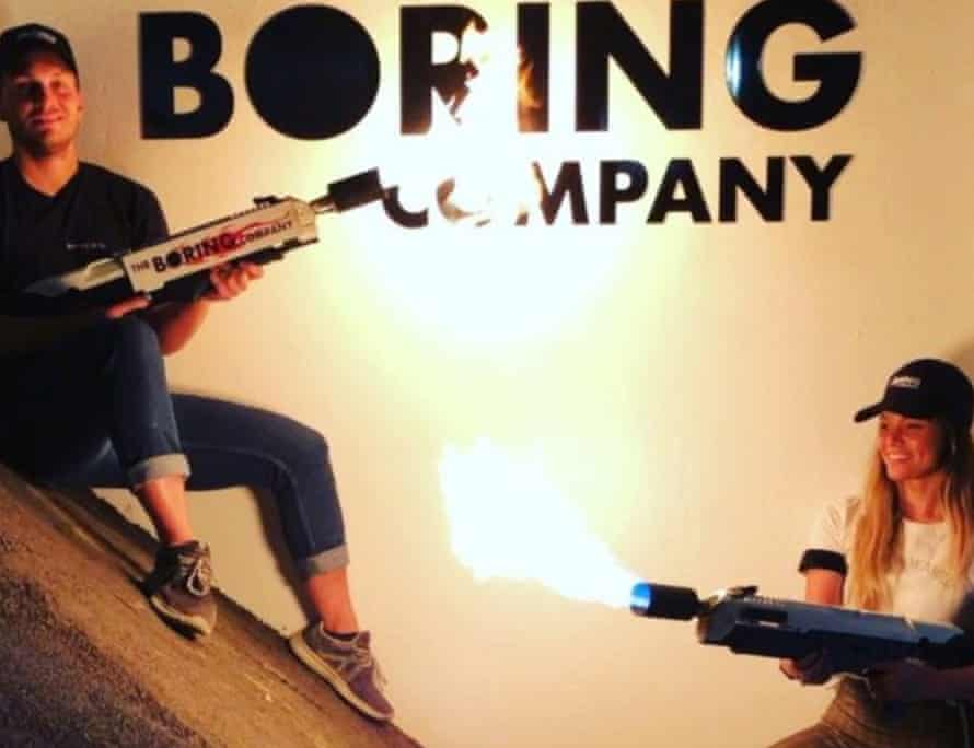 models pose with lighted boring company flamethrowers