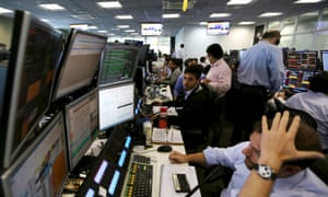 Traders at XP Investimentos brokerage in São Paulo after Standard & Poor's cut the country's sovereign rating to junk.