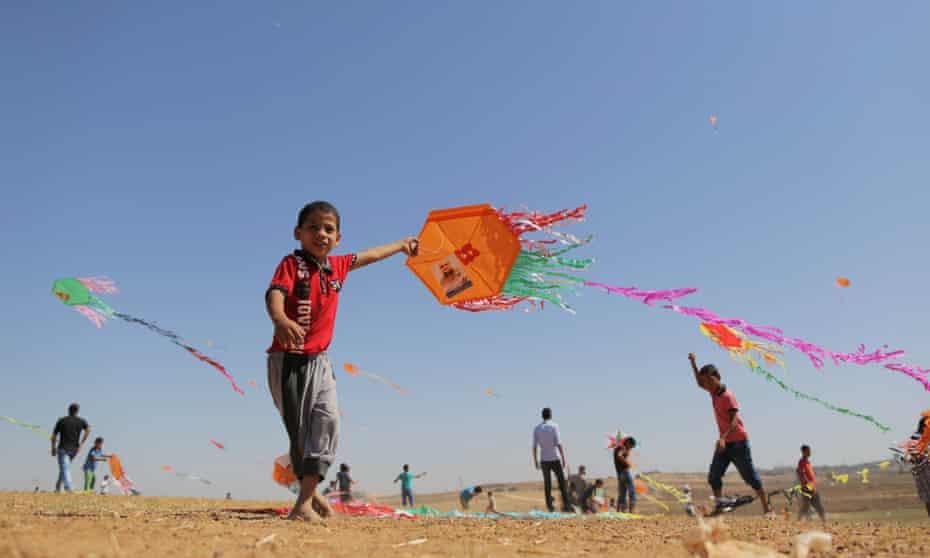 Palestinian children fly kites featuring images of Mohammed El Halabi in Beit Hanoun, Gaza.