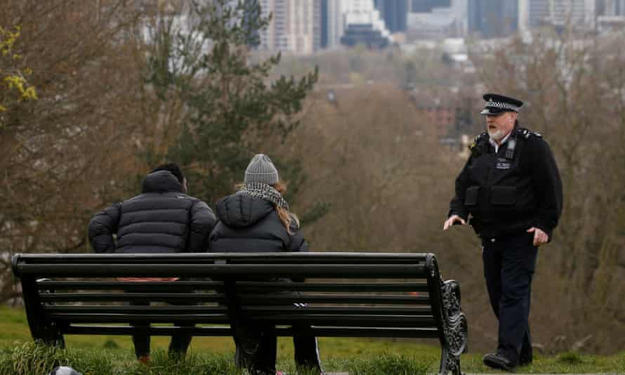 a male police officer talks to a man and a woman on a bench in Greenwich Park, London
