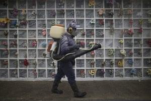 A cemetery worker fumigates niches inside Nuestra Señora de Belen cemetery amid the Covid-19 pandemic in Fusagasuga