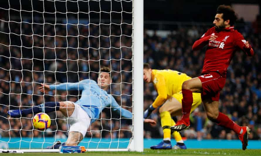 Manchester City's John Stones clears the ball off the line as Mohamed Salah approaches.