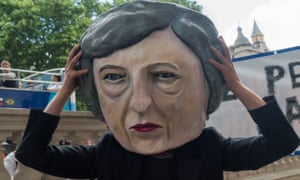 Protester wearing a caricature head of Theresa May