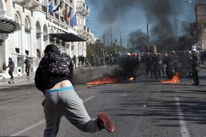 Greek police stand guard amid molotov cocktails thrown by protesters during a massive demonstration as part of a 24-hour general strike in Athens on November 12, 2015. Around 20,000 people demonstrated against fresh cuts in Athens, with sporadic outbreaks of violence, in the first general strike against the leftist government of Alexis Tspiras who swept to power on an anti-austerity ticket. AFP PHOTO / LOUISA GOULIAMAKILOUISA GOULIAMAKI/AFP/Getty Images