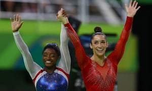Simone Biles, left, and Aly Raisman wave to the crowd as they wait for Biles' score after competing on the floor.