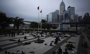 Protesters against a proposed extradition bill, rest near the Legislative Council building in the early morning in Hong Kong