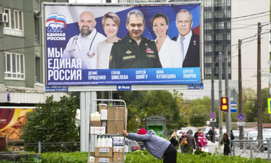 A store worker rolls a cart with groceries past election posters depicting candidates for the State Duma, the lower house of the Russian parliament.