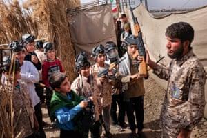 Children pretend to capture an Iraqi fighter