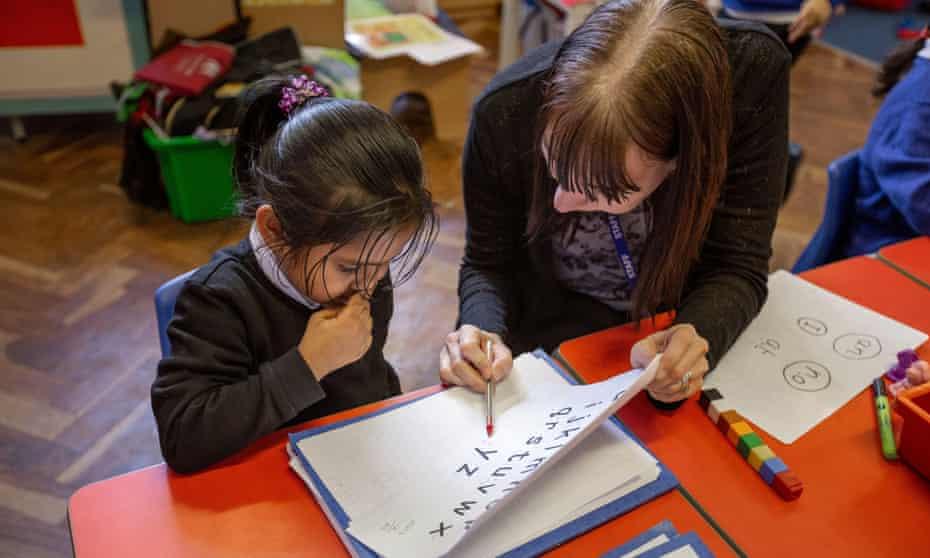 A teacher helps a pupil during an English class.