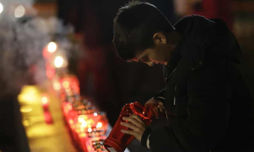 A boy lights a candle in Mostar.