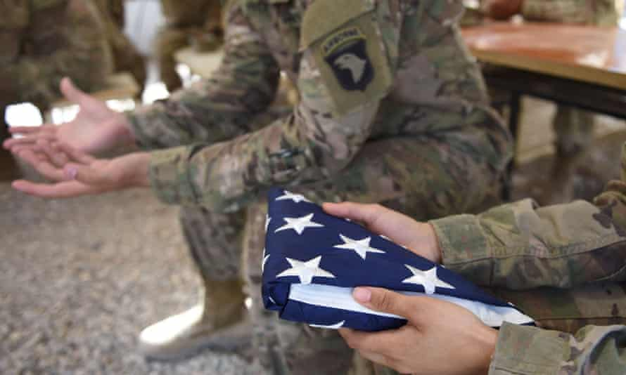 A US soldier holds the national flag ahead of a handover ceremony at Leatherneck Camp in the Afghan province of Helmand