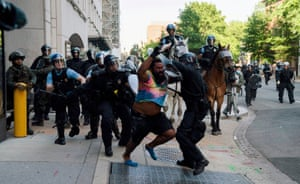 Washington, US Riot police chase a man as they clear Lafayette Park and the surrounding area before an appearance by President Trump
