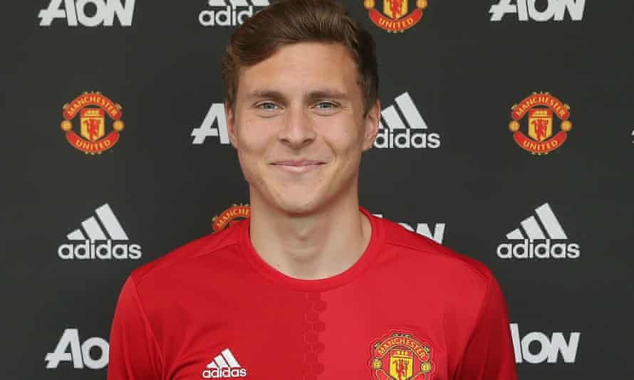 Victor Lindelof poses in a Manchester United shirt after signing for the club at Aon Training Complex.