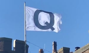 The flag denoting the QAnon conspiracy above the Camelot hotel.