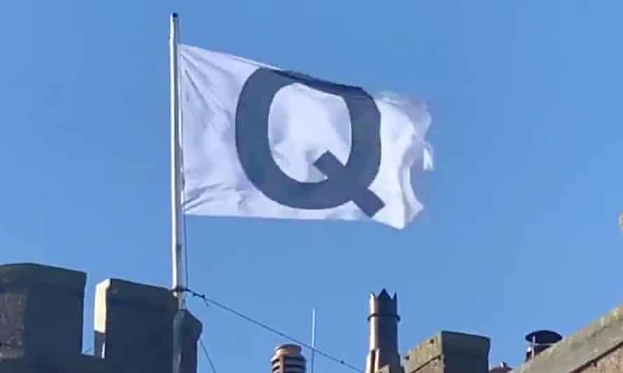 The flag denoting the QAnon conspiracy above the Camelot hotel.