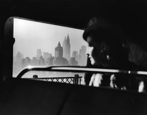 A female passenger on a bus traveling over the 59th Street bridge to Queens looks out south onto the hazy New York City midtown skyline, New York, New York, 1940s. Prominent structures include the Daily News building (left), the Empire State building (center, in the background) and the Chrysler building (right)