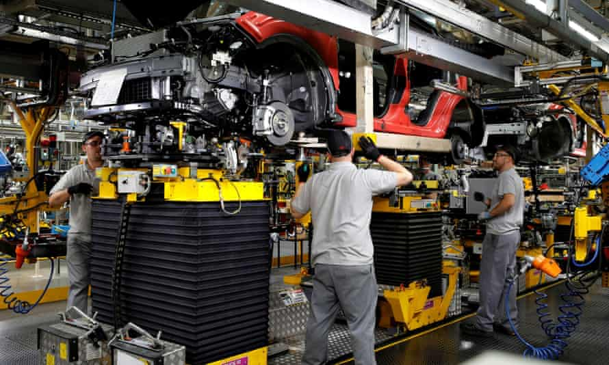 Workers are seen on the production line at Nissan's car plant in Sunderland, Britain