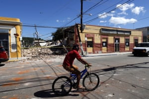 A man rides a bicycle in front of collapsed homes in Guayanilla