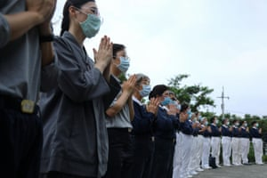 Members of the Tzu Chi foundation take part in a prayer as rescuers transfer bodies at Xincheng railway station