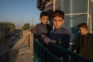 """Mujib, eight (front) with Siauddin, 10 (back) and Najmuddin, seven, stand on the balcony of their rented house in Kunduz in Northern Afghanistan. Siauddin says: """"My father is Kunduz's police commander and he fights the Taliban, that's why I am afraid of them. I'm scared for my father. I worry that he will be injured in fighting. Sometimes I hear about my father's friends being killed. One of them - Abdul - was like an uncle to me. We played and joked around. Now he's dead and I miss him. At night, we sometimes hear explosions and rockets. If peace doesn't come, I'll become a commander like my father and fight."""""""