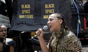 A member of the Black Lives Matters movement speaks to members as they stage a sit-in at the annual Pride parade in Toronto.