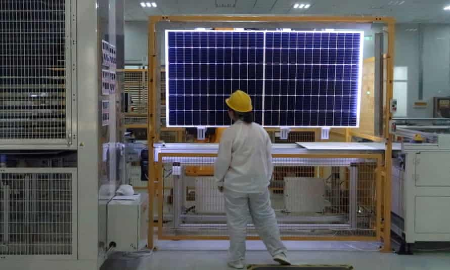 A worker conducts a quality check of a solar module product at a Longi factory in Xian, China
