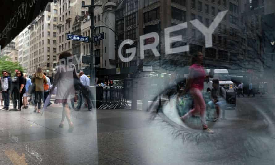 People walk past an advert for EL James's Grey.