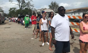 Residents wait in the heat to pick up a bag of ice in the heat in Wilmington, North Carolina, days after Hurricane Florence hit.
