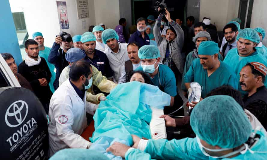 Medics carry an injured woman to the ambulance at a hospital after a suicide attack in Kabul