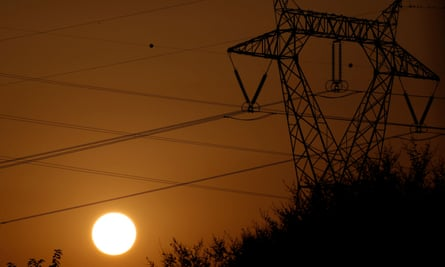 the sun behind electricity pylons