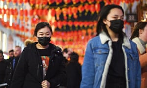 People wear masks in China Town, London, on Saturday.