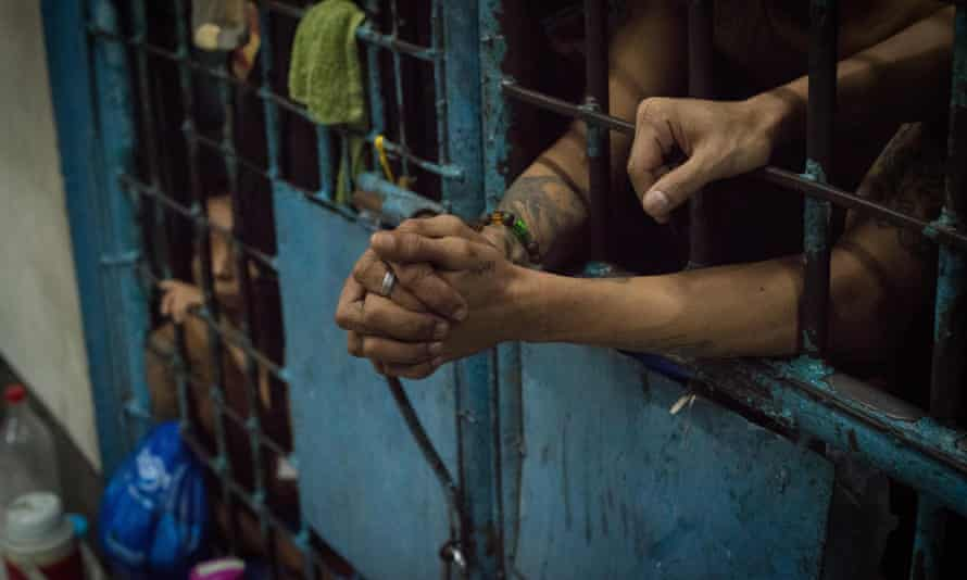 Inmates stay inside an overcrowded jail cell inside a police precint jail in manila