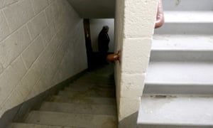 A detective with the district attorney's office inspects a stairwell at the Louis Pink Houses public housing complex in Brooklyn.