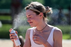 A woman sprays her face with thermal water at the Pokrovskiy Bereg beach