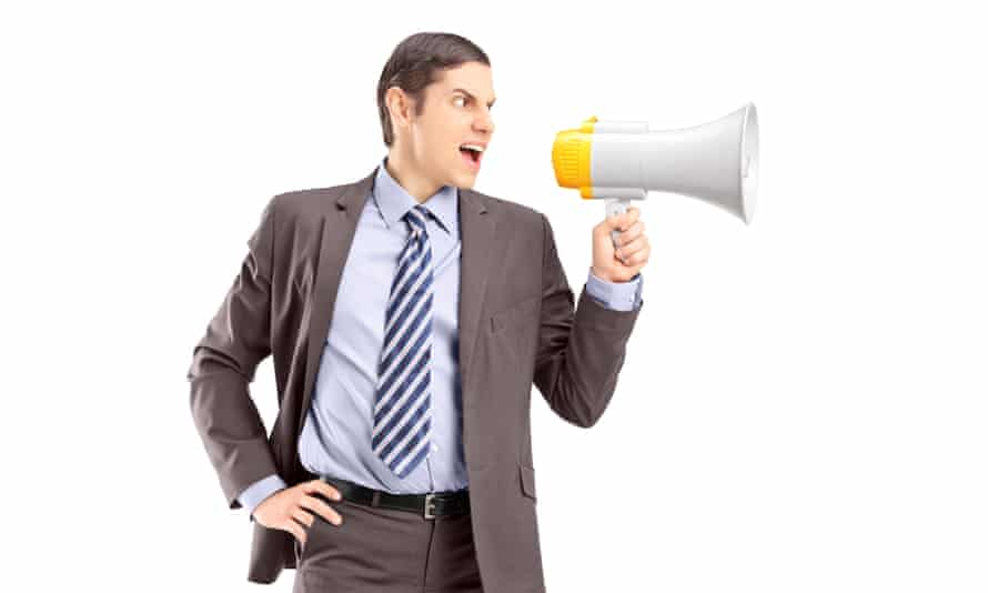 An angry young businessman announcing via megaphone isolated against white backgroundD54NB7 An angry young businessman announcing via megaphone isolated against white background