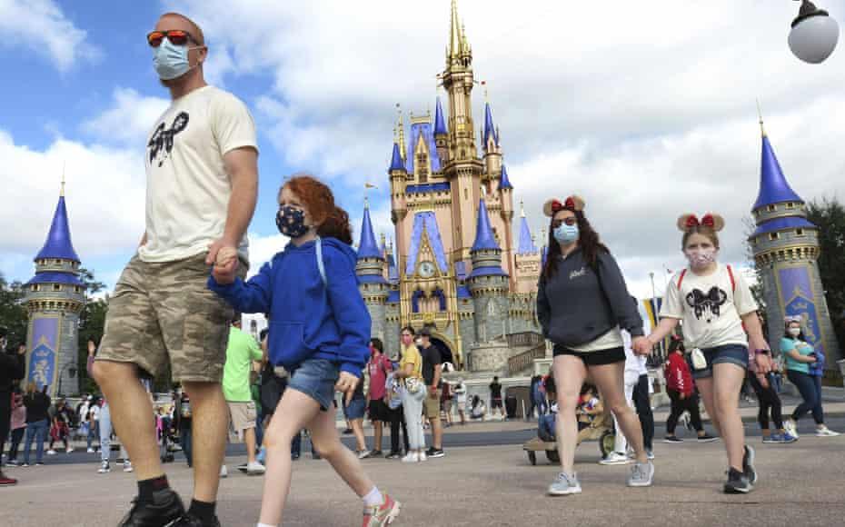 A family wearing masks walks past Cinderella's castle in the Magic Kingdom, at Walt Disney World in Lake Buena Vista, Florida, on 21 December.