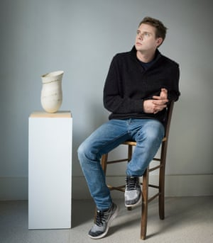 Jonathan Anderson sitting on a chair next to a plinth with a stoneware pot on top.
