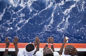 Malta: African migrants stand on the deck of the Aquarius vessel of SOS Mediterranee and Doctors Without Borders. They are being transferred to Italy after 265 people were rescued from the Mediterranean Sea over previous days